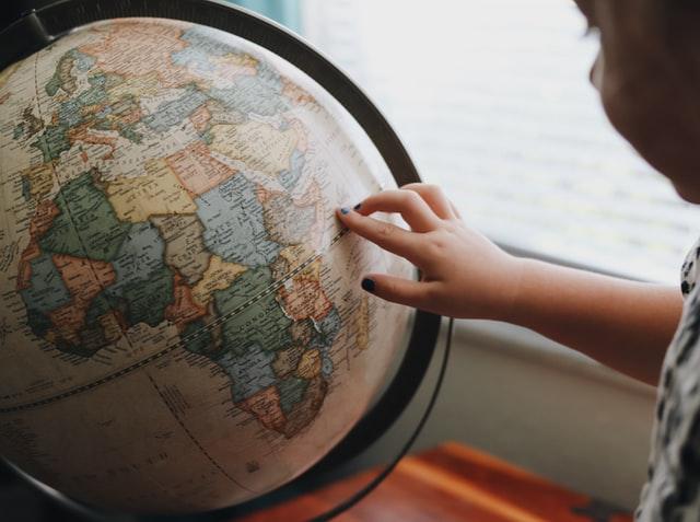 地球儀で行きたい国を探す子供