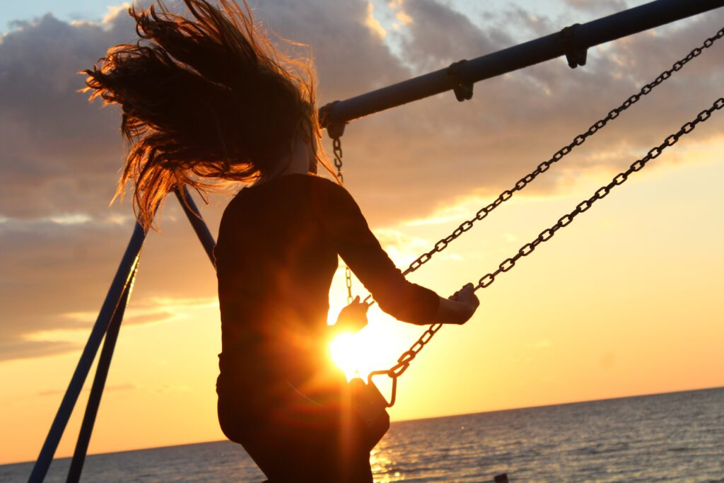 夕陽をバックにブランコに乗る女性