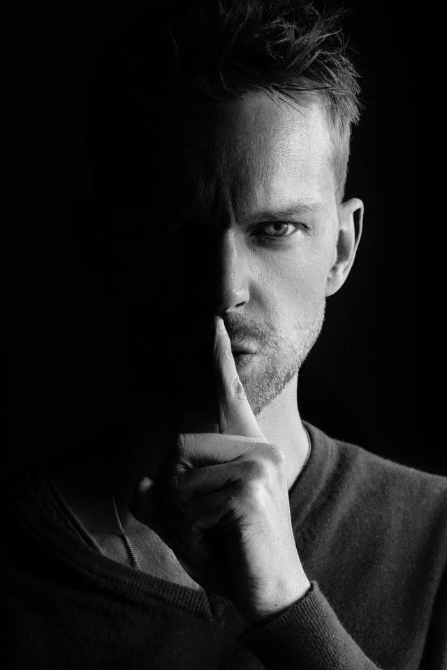 人差し指を立てて秘密を表現する男性